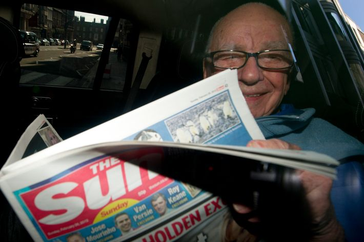 News Corporation Chief Rupert Murdoch holds up a copy of the newly launched 'The Sun on Sunday' newspaper as he leaves his London home on February 26, 2012.