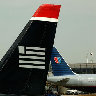 WASHINGTON - APRIL 08: Airplanes belonging to US Airways and United Airlines stand parked at their gates at Ronald Reagan National Airport April 8, 2010 in Washington, DC. The two airlines are in merger talks once again and if the deal goes through they would form one of the world's largest airlines. (Photo by Chip Somodevilla/Getty Images)