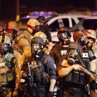 FERGUSON, MO - AUGUST 17:  Police advance on demonstrators protesting the killing of teenager Michael Brown on August 17, 2014 in Ferguson, Missouri. Police shot smoke and tear gas into the crowd of several hundred as they advanced near the police command center which has been set up in a shopping mall parking lot. Brown was shot and killed by a Ferguson police officer on August 9. Despite the Brown family's continued call for peaceful demonstrations, violent protests have erupted nearly every night in Ferguson since his death.  (Photo by Scott Olson/Getty Images)