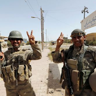 Iraqi soldiers gesture in center of Falluja