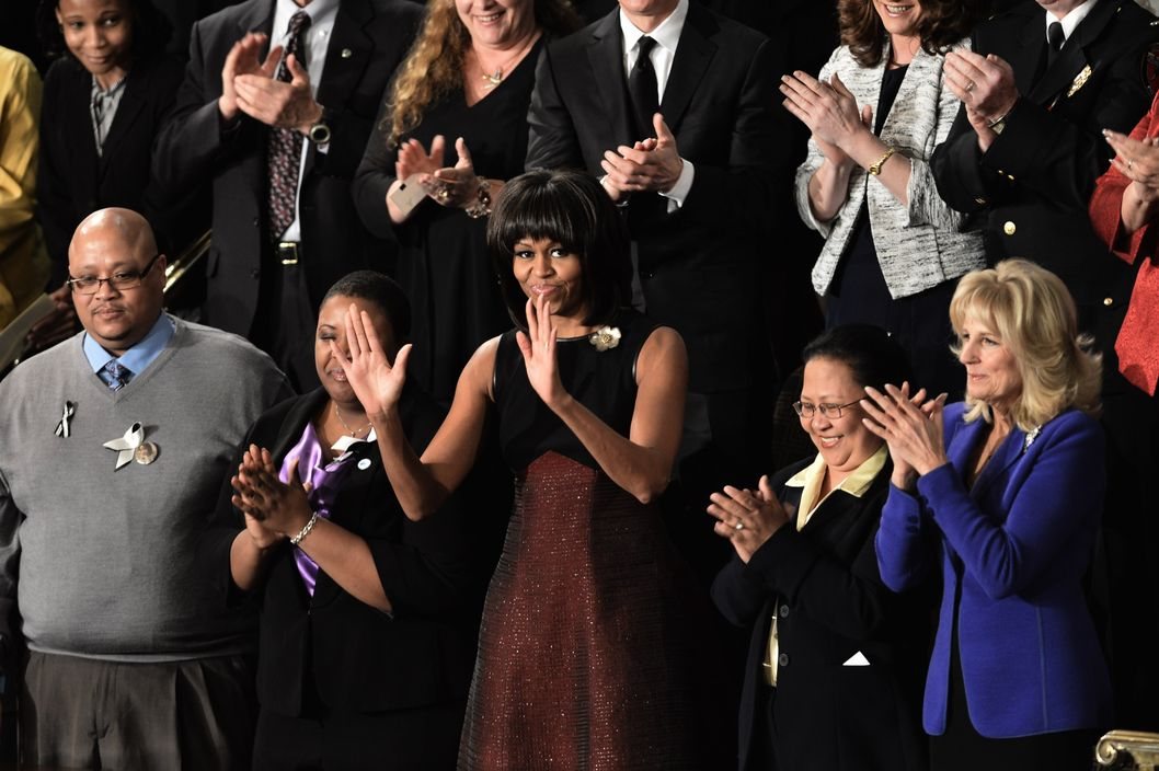 US First Lady Michelle Obama acknowledges applause as she arrives to attend President Barack Obama's annual State of the Union address to a joint session of Congress at the Capitol on February 12, 2013 in Washington.