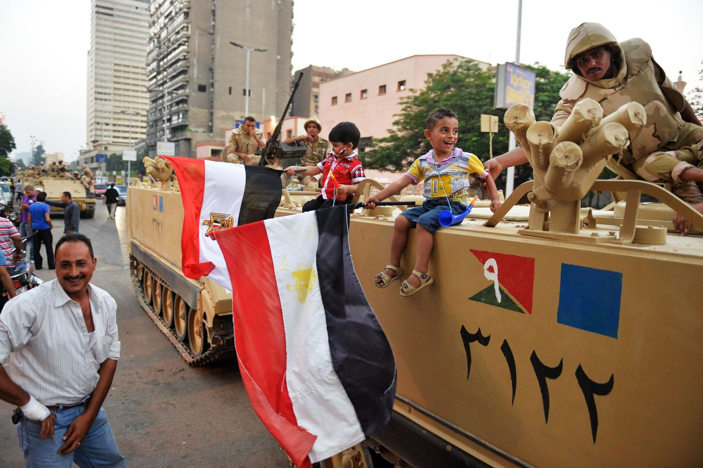Egyptian children hold national flags as they pose for pictures near army soldiers on an armoured personnel carrier (APC) in a Cairo street on July 3, 2013 after the Egyptian army deployed dozens of armoured vehicles near gathering of Islamist President Mohamed Morsi's supporters. Opposition leader Mohamed ElBaradei and the heads of the Coptic Church and Al-Azhar -- Sunni Islam's highest seat of learning -- will unveil an army roadmap for Egypt's future after President Mohamed Morsi, state television said.