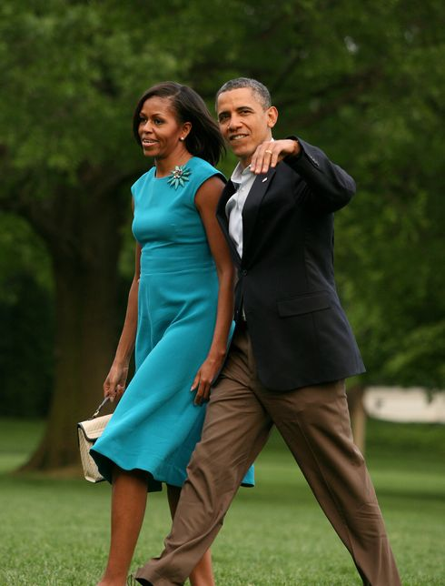 Barack and Michelle Obama walk across the White House lawn.