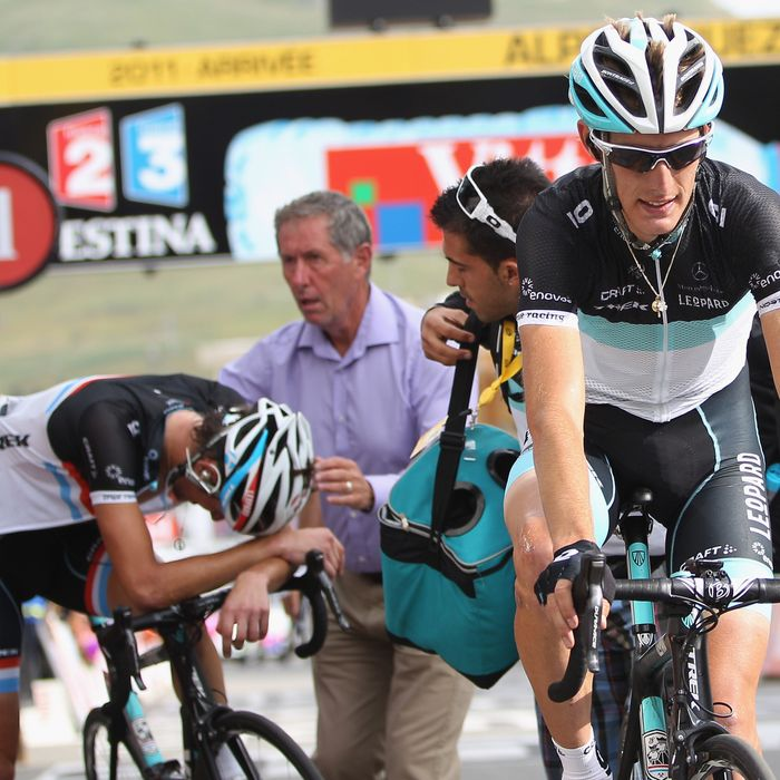 Andy Schleck crosses the finishing line alongside his exhausted brother Frank Schleck during Stage 19 of the 2011 Tour de France.