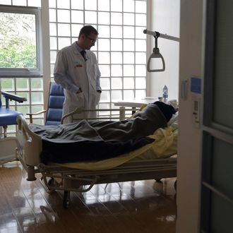 Doctor Stephane Mercier, Head of the palliative care unit, visits a patient at the palliative care unit of the AP-HP Paul-Brousse Hospital in Villejuif near Paris March 4, 2015.