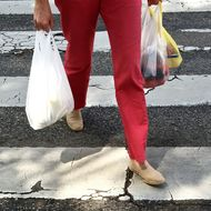 Low Section Of Woman Walking With Plastic Bags On Zebra Crossing