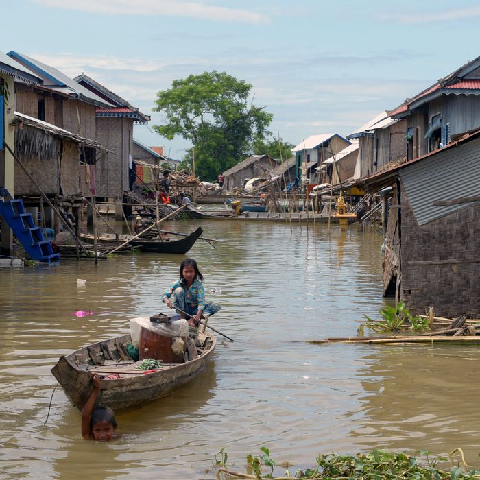 A girl in Kandal province, Cambodia, rows a boat through a flooded village.