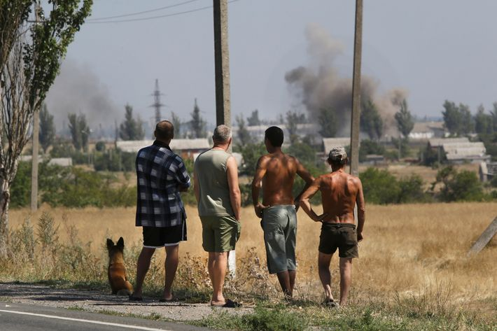 Local residents watch as smoke rises, during shelling, in the town of Novoazovsk, eastern Ukraine, Wednesday, Aug. 27, 2014. Separatist rebels shelled a town in southeastern Ukraine on Wednesday, raising fears they are launching a counter-offensive on government-held parts of the region, one day after the leaders of Ukraine and Russia met to discuss the escalating crisis. (AP Photo/Sergei Grits)