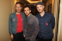 LONDON, ENGLAND - OCTOBER 24:  (UK TABLOID NEWSPAPERS OUT) Jonny Buckland, Chris Martin and Guy Berryman of Coldplay pose in the press room with their Best Act in the World Today Award at The 2011 Q Awards at The Grosvenor House Hotel on October 24, 2011 in London, United Kingdom.  (Photo by Dave Hogan/Getty Images)