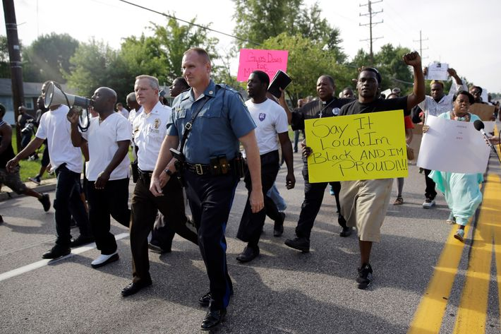 Thousands of demonstrators peacefully march down a street with members of the St. Louis County Police and Missouri Highway Patrol Thursday, Aug. 14, 2014, in Ferguson, Mo. The Missouri Highway Patrol seized control of a St. Louis suburb Thursday, stripping local police of their law-enforcement authority after four days of clashes between officers in riot gear and furious crowds protesting the death of an unarmed black teen shot by an officer. (AP Photo/Jeff Roberson)