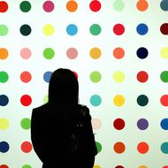 "New York, UNITED STATES: A member of the public walks past the painting ""Strontium 500"" by Damien Hirst during a preview 14 May 2007, for the 2007 Sale of Contemporary Art at Sotheby's New York. The sale will be held 15 May. This season's impressionist, modern and contemporary art sales in New York are expected to see several major records fall, especially in the contemporary artworks section.   AFP PHOTO/ TIMOTHY A. CLARY (Photo credit should read TIMOTHY A. CLARY/AFP/Getty Images)"