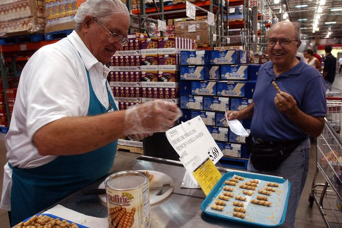A man distributing cookie samples to a delighted customer at Costco