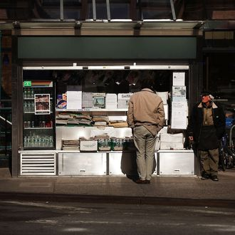 Jerry Delakas, 63, (R) a longtime newspaper vendor in Manhattan's Cooper Square, stands by his newsstand on April 3, 2012 in New York City.