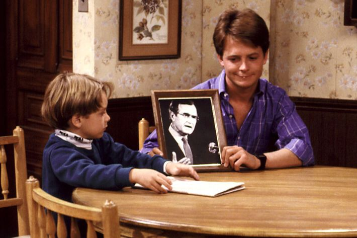FAMILY TIES, Brian Bonsall, Michael J. Fox, Alex Keaton holds a picture of President Bush. Yr.7, Ep, (Heartstrings), 12/4/88, 1982-89.