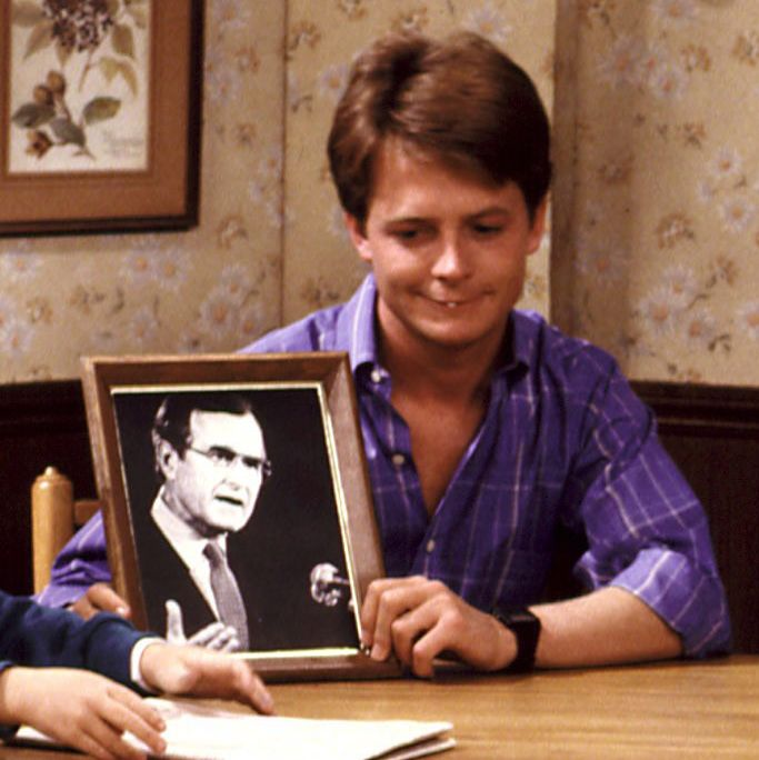 FAMILY TIES, Brian Bonsall, Michael J. Fox, Alex Keaton holds a picture of President Bush. Yr.7, Ep, (Heartstrings), 12/4/88, 1982-89.