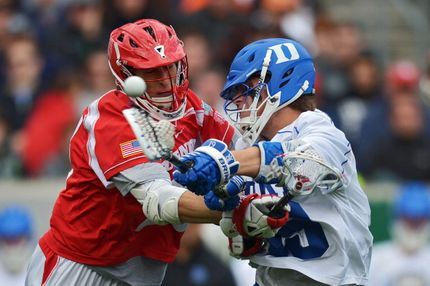 Cody Levine #23 of Cornell University Big Red hits Christian Walsh #19 of the Duke University Blue Devils while he shoots during a semifinal game of the 2013 NCAA Division I Men's Lacrosse Championships at Lincoln Financial Field on May 25, 2013 in Philadelphia, Pennsylvania. Duke won 16-14.