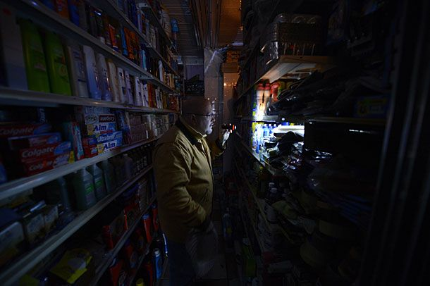 A man shops for groceries by flashlight at an East Village grocery store in New York on October 30, 2012 as New Yorkers cope with the aftermath of Hurricane Sandy. The storm left large parts of New York without power and transportation.     AFP PHOTO / TIMOTHY A. CLARY        (Photo credit should read TIMOTHY A. CLARY/AFP/Getty Images)