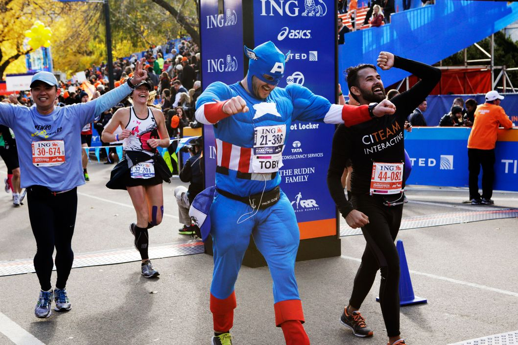 Runners, including a man wearing a Captain America costume, react as they cross the finish line after completing the New York City marathon, Sunday, Nov. 3, 2013, in New York. (AP Photo/Kathy Willens)