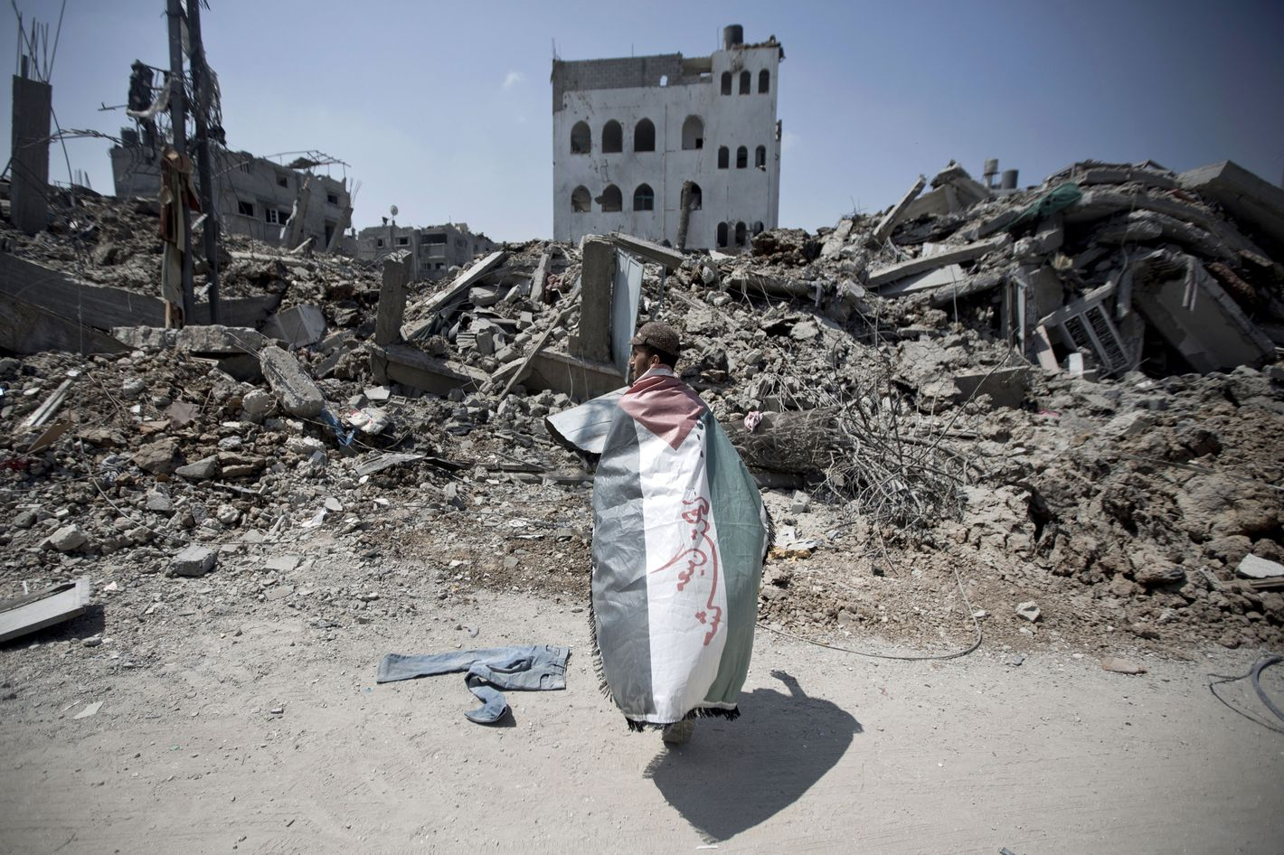 A Palestinian man, wrapped in his national flag, inspects the rubble of destroyed buildings and houses in the Shejaiya residential district of Gaza City, on July 28, 2014, on the beginning of the Muslim Eid festival ending the month-long fast of Ramadan. More than 6,200 Palestinians have been injured so far in the ongoing violence which began with an intensive air campaign on July 8 and expanded when Israel sent ground troops into the Gaza periphery on July 17.
