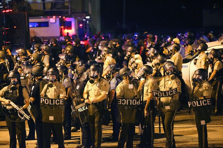 FERGUSON, MO - AUGUST 17: An large group of police officers advance toward demonstrators protesting the killing of teenager Michael Brown on August 17, 2014 in Ferguson, Missouri. Police shot smoke and tear gas into the crowd of several hundred as they advanced near the police command center which has been set up in a shopping mall parking lot. Brown was shot and killed by a Ferguson police officer on August 9. Despite the Brown family's continued call for peaceful demonstrations, violent protests have erupted nearly every night in Ferguson since his death.  (Photo by Scott Olson/Getty Images)