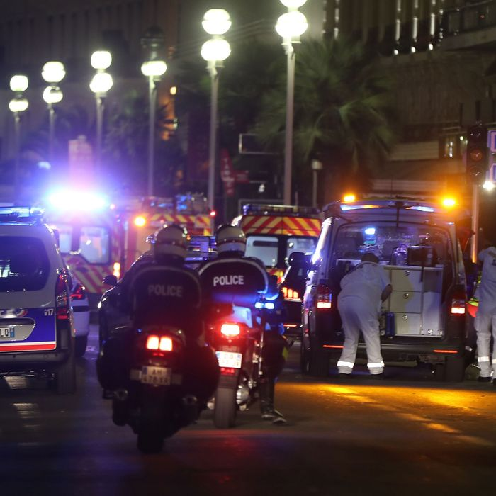 Police officers and rescue workers arrive at the scene of an attack on July 14, 2016, after a van plowed into a crowd leaving a fireworks display in the French Riviera town of Nice.
