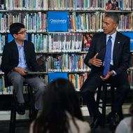"30 Apr 2015, Washington, DC, USA --- US President Barack Obama (R), with student moderator Osman Yaya (L), responds to a question while participating in a ""Virtual Field Trip"" with middle school students from around the country at Anacostia Library in Washington, DC, USA, 30 April 2015. Students from around the country will discuss new efforts to strengthen learning opportunities by improving access to digital reading content and public libraries. --- Image by ? SHAWN THEW/pool/Corbis"