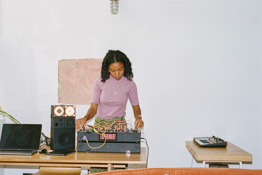 A woman standing at a modular synthesizer