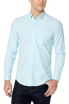 A male model wearing an Amazon Essential solid light blue slim-fit long-sleeve button down Oxford shirt.The Strategist - A Bunch of Men's Button Downs (From $16) Are on Sale at Amazon