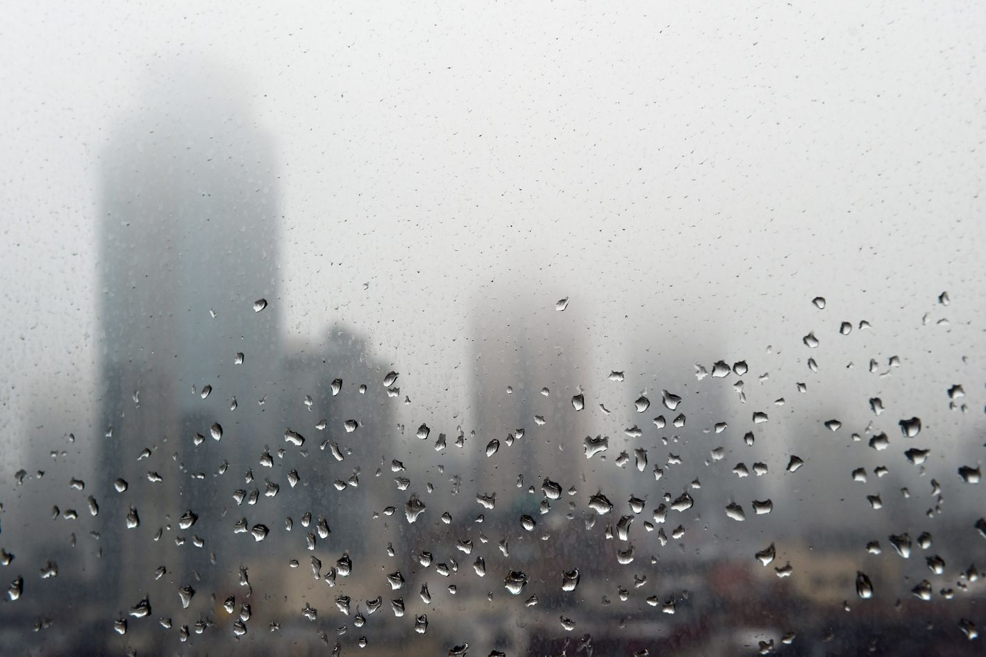 Raindrops are seen on a window as morning fog obscures the top floors of high rise buildings on the east side of Manhattan May 1, 2014 in New York.