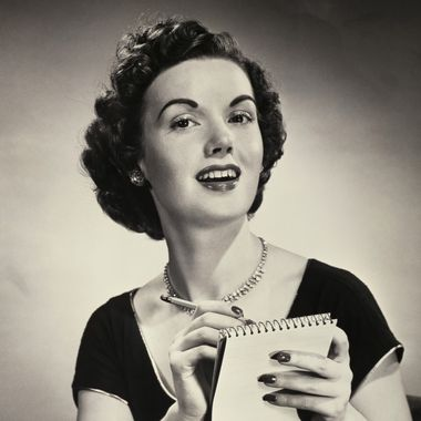 Portrait of a young woman writing on a notepad