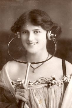 British music-hall star Zena Dare models a pair of turn-of-the-century headphones.