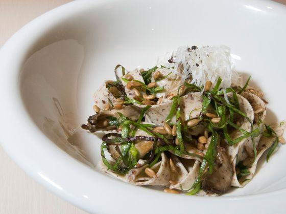 Quinoa tagliatelle with beet greens, maitake mushrooms, and sunflower kernels.