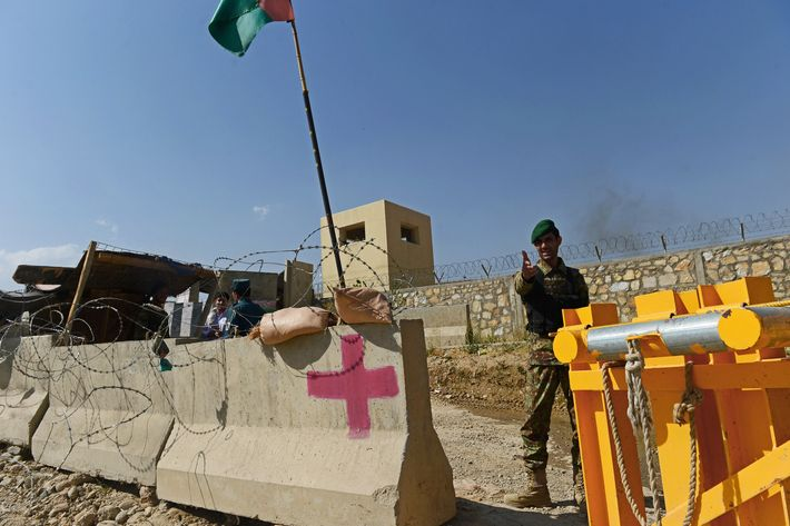 An Afghan National Army soldier gestures outside the gates of a British-run military academy, where an Afghan soldier opened fire on NATO troops inside the premises, on the outskirts of Kabul on August 5, 2014.  An Afghan soldier opened fire on NATO troops at a British-run military academy in Kabul on August 5, officials said, adding that casualty details were unconfirmed and the cause of the shooting was unclear.