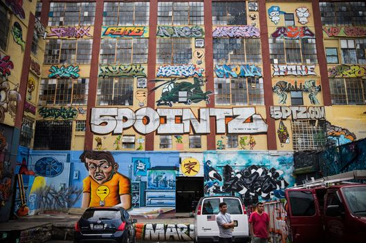 "People stand near the ""5 Pointz"" building on August 9, 2013 in the Long Island City neighborhood of the Queens borough of New York City. 5 Pointz is a series of properties that graffiti artists use as an outdoor art exhibit space - it is considered the Mecca of the graffiti world. The space has been used as a space for graffiti artists since the early 1990s, though in 2011, Jerry Wolkoff, the owner of the property, announced he planned to demolish the building to build high-rise residential buildings. The 5 Pointz graffiti community has since been in a battle to keep the space as is; they are currently petitioning the government to consider the space a protected cultural landmark."