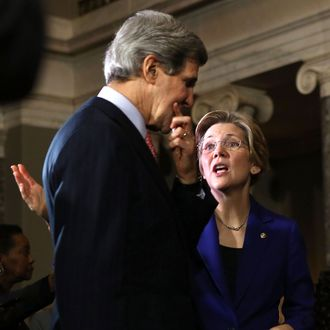 U.S. Sen. Elizabeth Warren (D-MA) (R) talks to Secretary of State and former U.S. Sen. John Kerry (D-MA) (L) during a re-enactment of the swearing-in for U.S. Senator William
