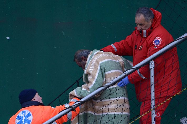 "A wounded passenger (C) among 49 survivors evacuated from the burning ferry ""Norman Atlantic is helped by rescuers to disembark as he arrives in the harbor of Bari on board the ship ""Siprit of Piraeus"" on December 29, 2014.  Rescuers battled in the dark to save hundreds of passengers still trapped on a burning Italian ferry adrift off Albania in the early hours of December 29, as coastguards reported one man had died in the high-seas drama."
