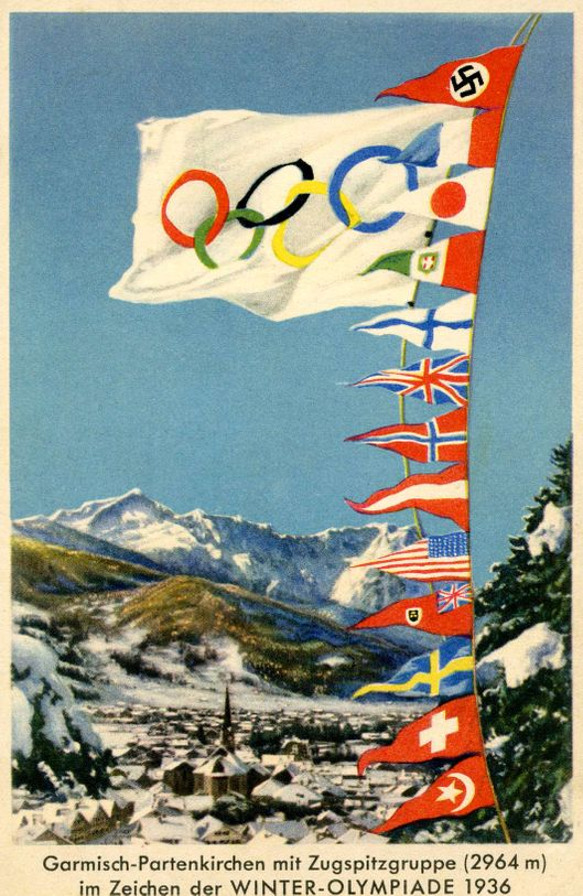 Winter Olympics 1936   Germany   Olympics symbol of interlinking Olympic Rings on flag, plus Third Reich Swastika and flags from UK, USA, Switzerland etc flying above the Zugspitze  ( 2,964 metres above sea level)- the highest mountain in Germany. Located at the Austrian border in  town of Grainau in district of Garmisch-Partenkirchen, Bavaria.  (Photo by Culture Club/Getty Images)