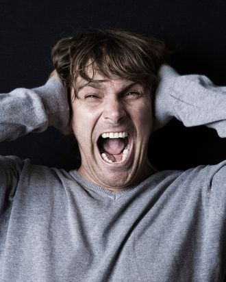 Man screaming with hands covering ears