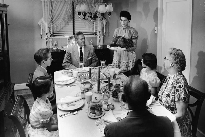 A family sits at a formally prepared dinner table, looking eager as a woman brings a roast turkey to the table on a platter, 1950s.