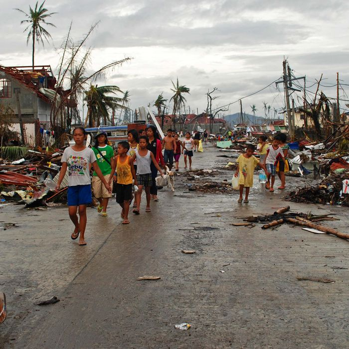 LEYTE, PHILIPPINES - NOVEMBER 12: Survivors of the typhoon walk through a devastated area on November 12, 2013 in Leyte, Philippines. Four days after the typhoon devastated the region many have nothing left, they are without food or power and most lost their homes. Around 10,000 people are feared dead in the strongest typhoon to hit the Philippines this year. (Photo by Dondi Tawatao/Getty Images)