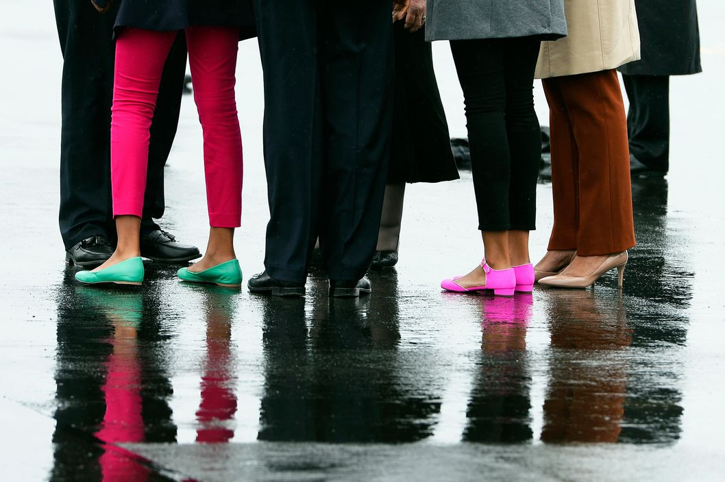 A picture shows the footwear of US President Barack Obama (2L), First Lady Michelle Obama (R) and their daughters Malia (2R) and Sasha (L) as they stand on the tarmac after disembarking from Air Force One at Aldergrove International Airport in Belfast, Northern Ireland on June 17, 2013 as Barack Obama prepared to attend the G8 summit in Lough Erne near Enniskillen.