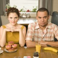 Couple sitting in diner with doughnuts and fruit, portrait