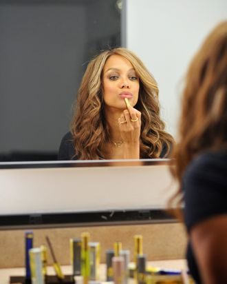 Tyra Banks applying lipstick from her Tyra Beauty line.