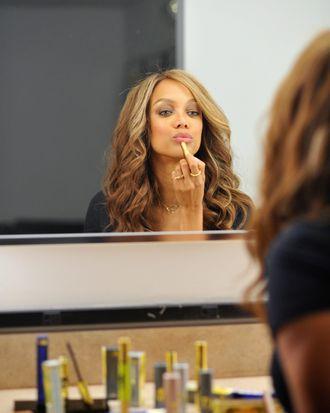 Tyra Banks applying lipstick from her Tyra Beauty line.