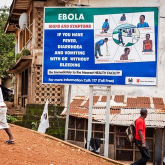 People walk past a billboard encouraging people suffering from symptoms linked to Ebola to present themselves at a health facility for treatment in Freetown, Sierra Leone, Thursday, Aug. 7, 2014. While the Ebola virus outbreak has now reached four countries, Liberia and Sierra Leone account for more than 60 percent of the deaths, according to the World Health Organization. The outbreak that emerged in March has claimed at least 932 lives. (AP Photo/ Michael Duff)