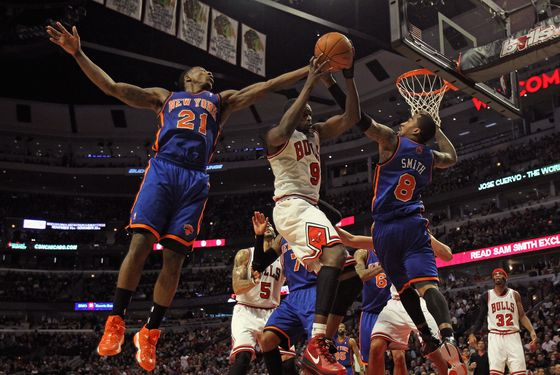 CHICAGO, IL - APRIL 10: Loul Deng #9 of the Chicago Bulls rebounds between Iman Shumpert #21 and J.R. Smith #8 of the New York Knicks at the United Center on April 10, 2012 in Chicago, Illinois. The Bulls defeated the Knicks 98-86.