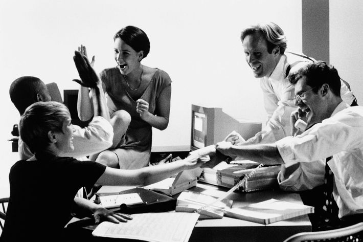 Group of executives celebrating in boardroom (B&W)