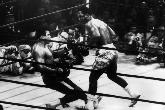 March 1971:  In a title fight at Madison Square Gardens, New York, Muhammad Ali goes down in the 15th round to a left hook from world heavyweight champion Joe Frazier who kept the title with an unanimous points win. Cameramen are crowded round the ring.  (Photo by Keystone/Getty Images)