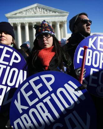 Pro-choice activists hold signs as marchers of the annual March for Life arrive in front of the U.S. Supreme Court January 22, 2014 on Capitol Hill in Washington, DC. Pro-life activists from all around the country gathered in Washington for the event to protest the Roe v. Wade Supreme Court decision in 1973 that helped to legalize abortion in the United States.