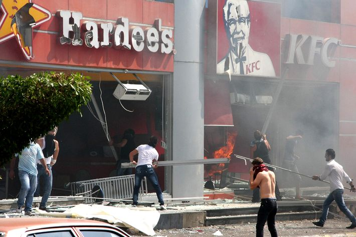 "Lebanese men ransack US fast food chains Hardee's and KFC as they protest against the controversial film ""Innocence of Muslims"" in the northern Lebanese city of Tripoli on September 14, 2012. The low-budget movie, which ridicules the Prophet Mohammed and portrays Muslims as immoral and gratuitously violent, has triggered protests in several countries."